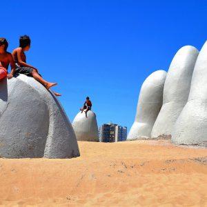 Boys Sitting on La Mano, The Hand, on Brava Beach in Punta del Este, Uruguay - Encircle Photos